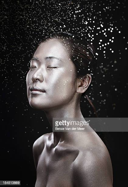 Asian woman in silver with sparkles in air.