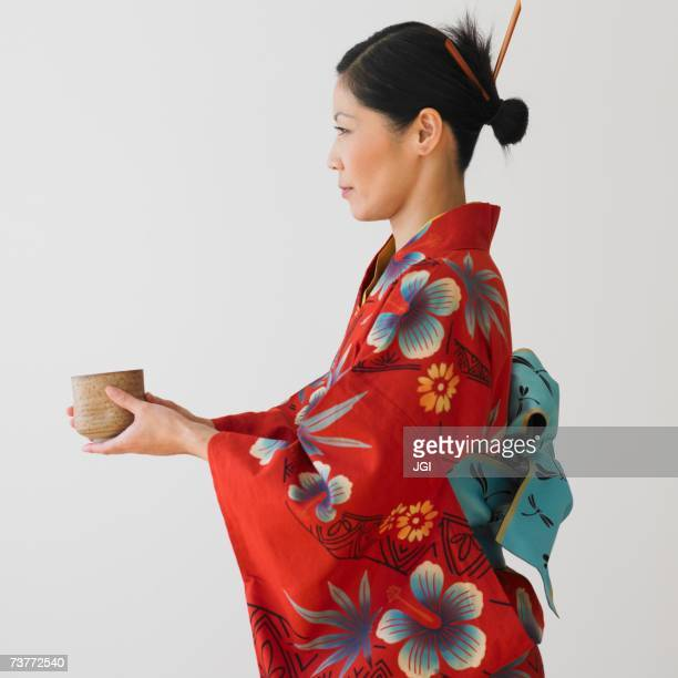 Asian woman in traditional dress holding bowl