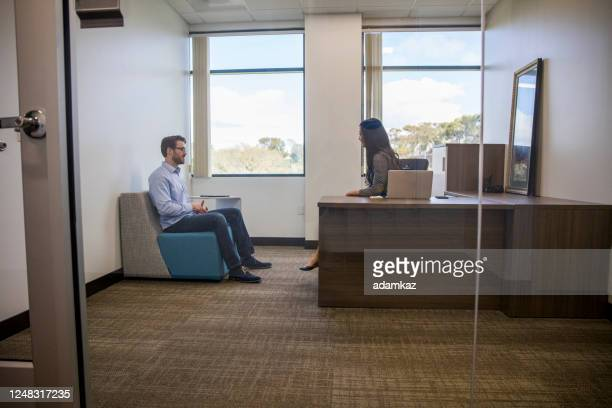 asian woman interviewing a young man for a job - audition stock pictures, royalty-free photos & images