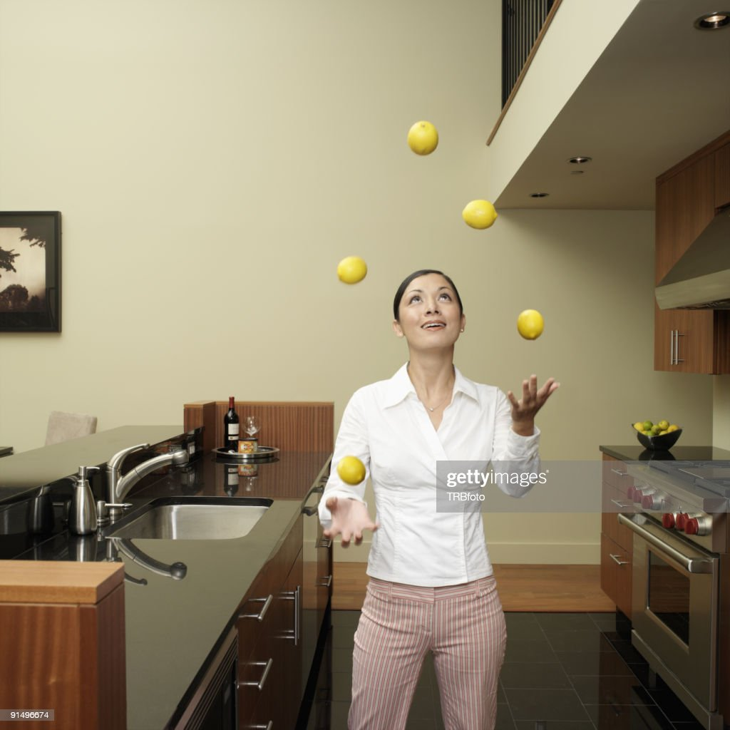 Asian Woman Juggling Lemons In Kitchen Stock Photo | Getty Images