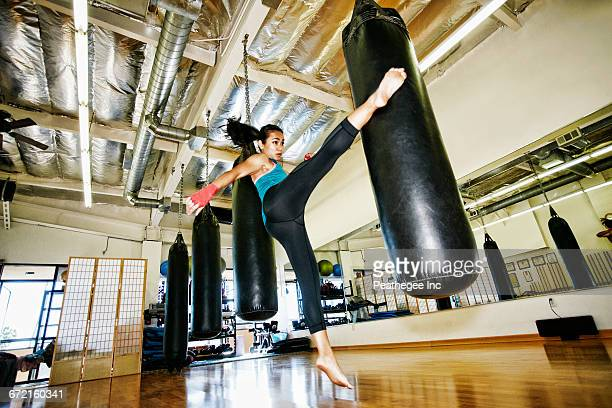 asian woman kicking heavy bag in gymnasium - patadas fotografías e imágenes de stock