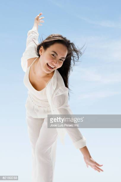 Asian woman laughing and bending forward