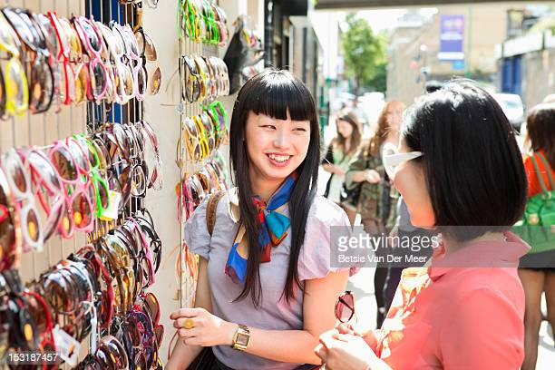 Asian woman laughs at friend trying on sunglasses.