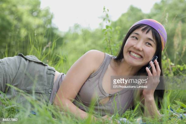 Asian woman laying in grass talking on cell phone