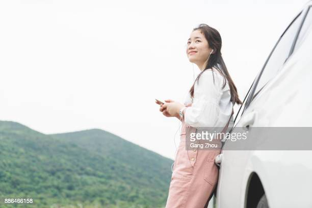 asian woman leaning against car listening to music - leaning stock pictures, royalty-free photos & images