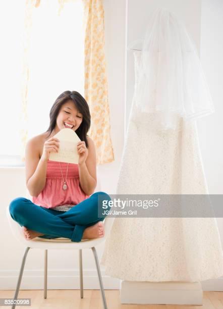 Asian woman licking wedding invitation