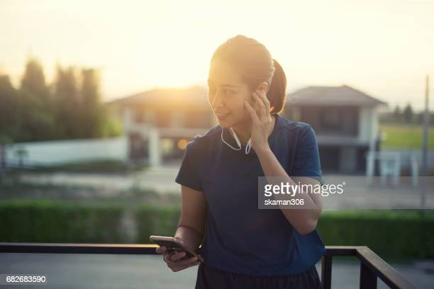 Asian woman listen music and feeling relaxing after finish work out