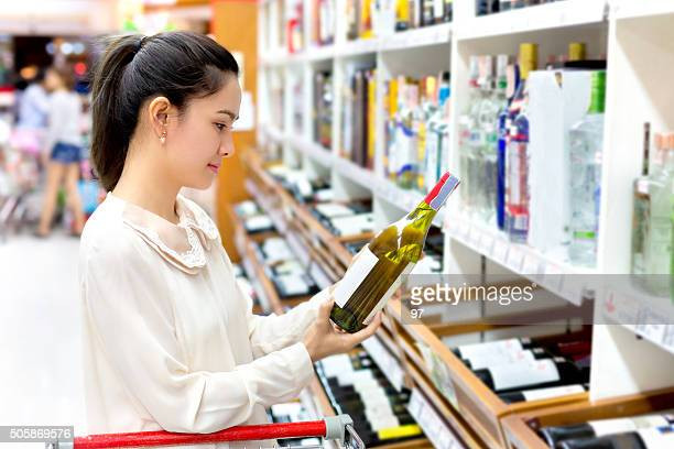 Asian Woman Looking at Bottle of Wine.
