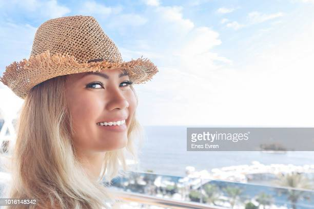 Asian woman looking at camera and smiling with straw hat in holiday vacation