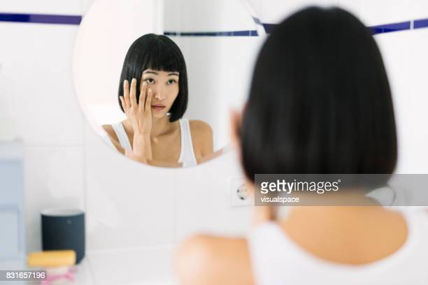 Asian Woman looking at her mirror image in the bathroom