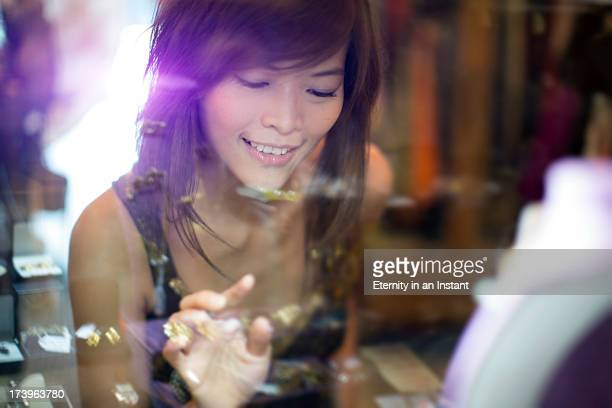 Asian woman looking at jewelry in  window display