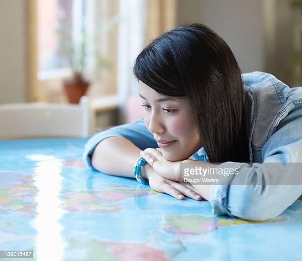 Asian woman looking at world map.