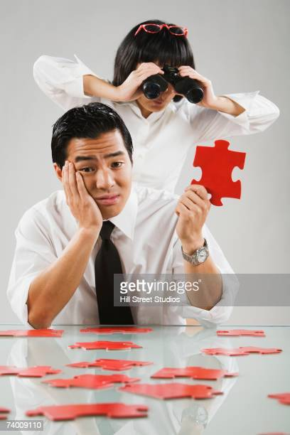 Asian woman looking through binoculars at puzzle piece