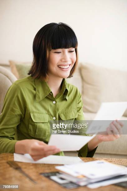 asian woman looking through mail - post structure stock photos and pictures