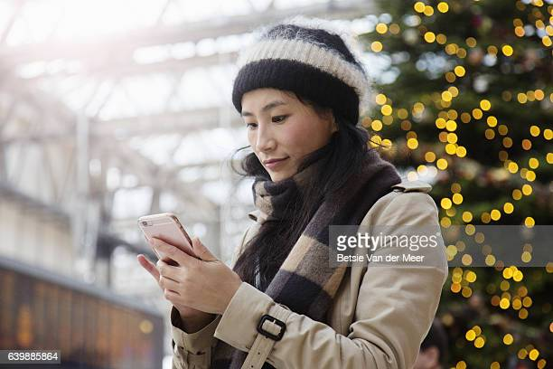 Asian woman looks at her phone in railroad station.