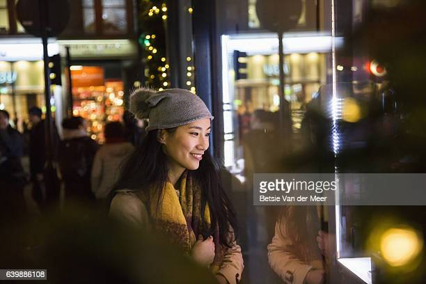 Asian woman looks in shopwindow at night time.