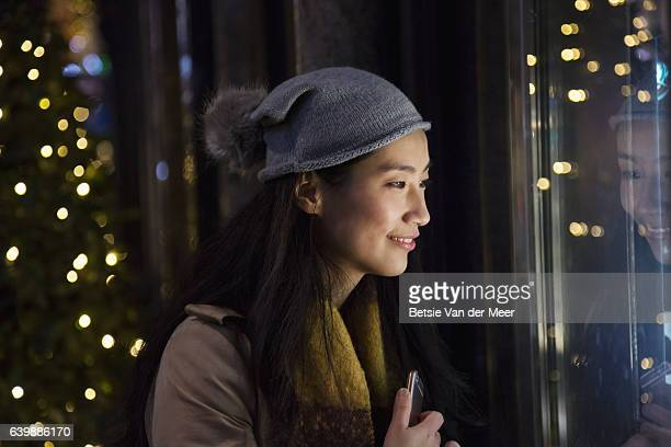 asian woman looks into shopwindow at night time. - 欲望 ストックフォトと画像