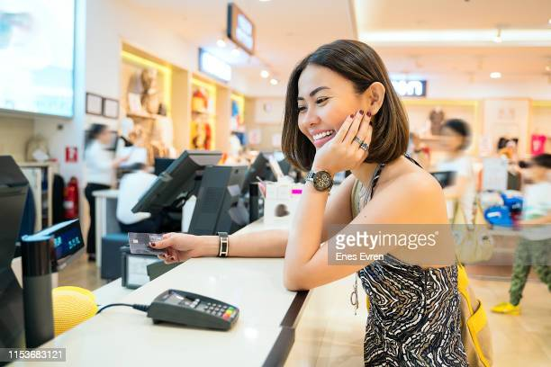 Asian woman making credit card payment in clothing shop