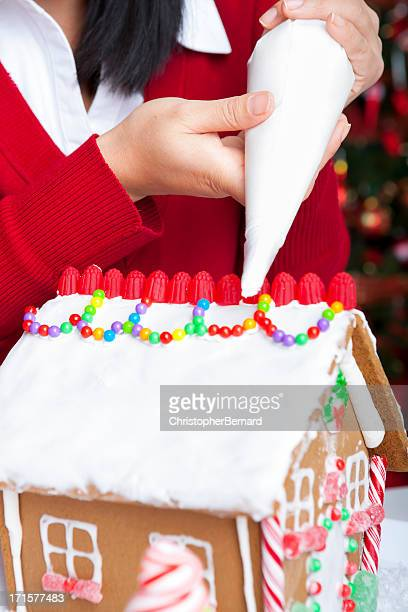 Asian woman making gingerbread house