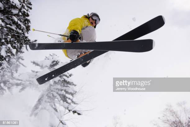 Asian woman on skis mid-air