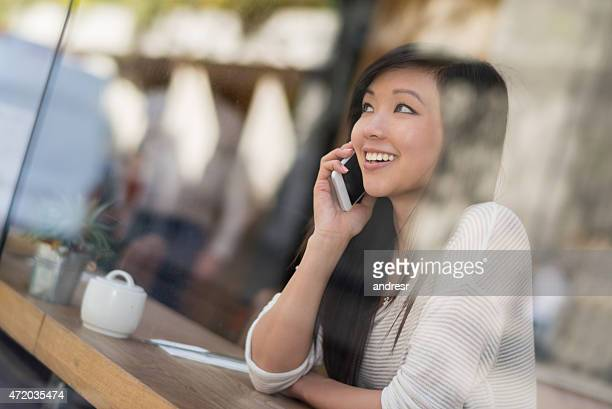 Asian woman on the phone at a cafe