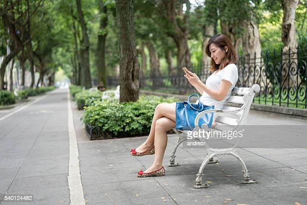 Asian woman outdoors using her smart phone