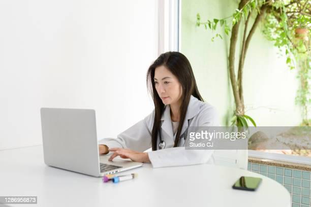 asian woman performing patient care using portable device - portable information device imagens e fotografias de stock