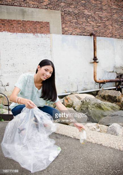 asian woman picking up litter - city cleaning stock pictures, royalty-free photos & images