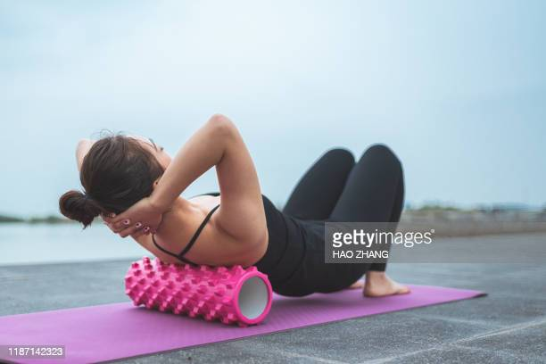 asian woman pilates instructor stretching and warming up using foam rolle - de rola imagens e fotografias de stock