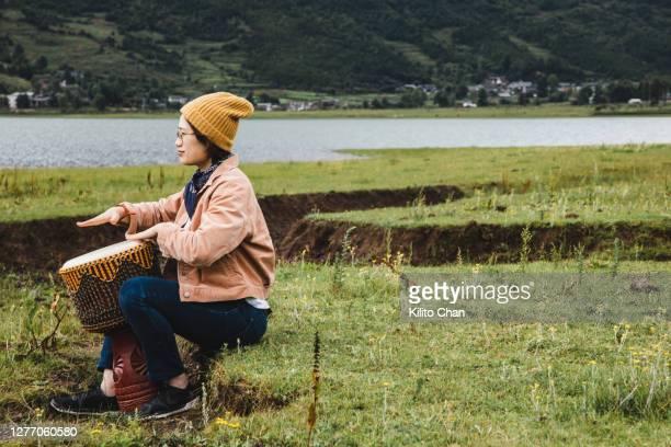 asian woman playing bongo outdoor in the wild nature - darstellender künstler stock-fotos und bilder