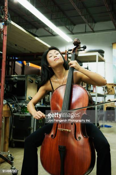 asian woman playing cello in warehouse - cellist stock pictures, royalty-free photos & images
