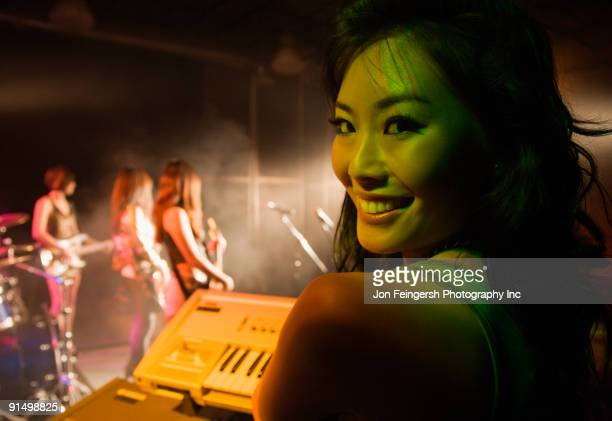 Asian woman playing keyboard onstage
