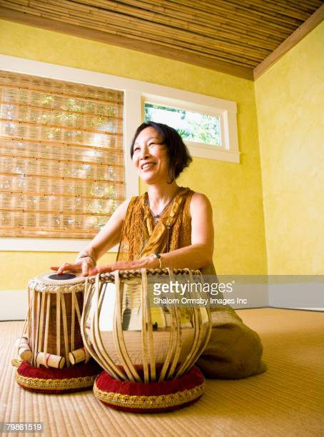 Asian woman playing table drums