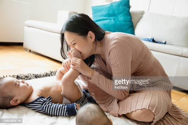 asian woman playing with her babies sitting on the rug - kissing feet stock pictures, royalty-free photos & images