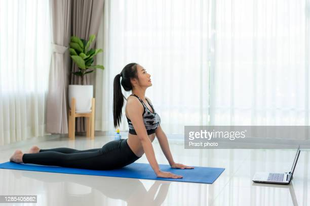 asian woman practice or exercise indoor cobra pose while watching videos fitness workout class live streaming online on laptop in the living room at home. - 服従訓練 ストックフォトと画像