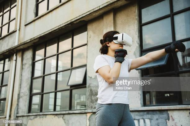 asian woman practicing boxing using vr technology - combat sport photos et images de collection