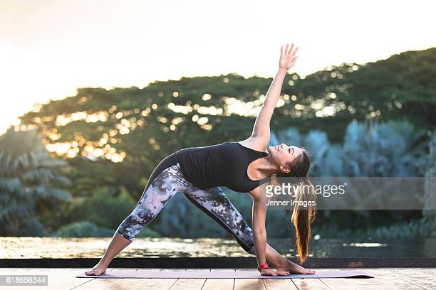 Asian woman practicing Triangle Pose yoga at dusk.