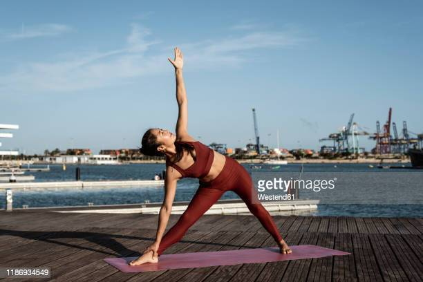 asian woman practicing yoga at harbour, triangle pose - bra top stock pictures, royalty-free photos & images