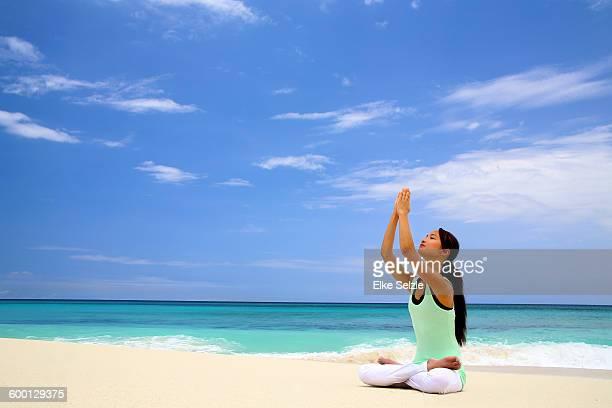 Asian woman practicing yoga on tropical  beach