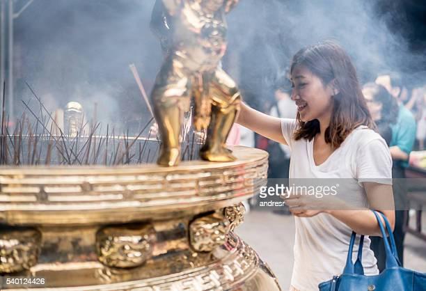 asian woman praying at a buddhist temple - boeddhisme stockfoto's en -beelden