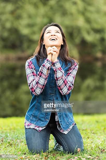 asian woman praying in a park - mulher orando de joelhos imagens e fotografias de stock