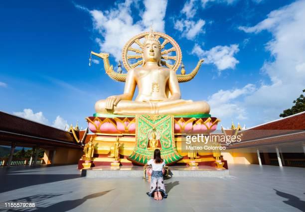 asian woman praying in front of the big buddha, ko samui, thailand - mulher orando de joelhos imagens e fotografias de stock