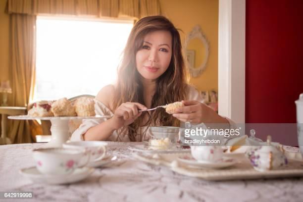 Asian woman preparing tea and scones at home