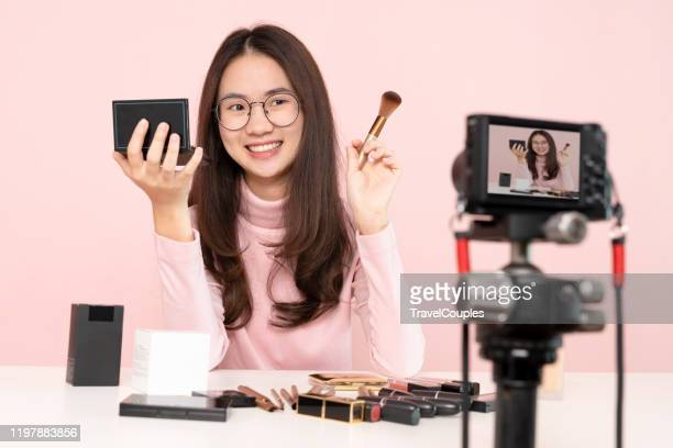 asian woman professional beauty vlogger or blogger live broadcasting cosmetic makeup tutorial viral video clip by camera sharing on social media. business online influencer on social media concept. online selling. online shopping - tutorial stock pictures, royalty-free photos & images