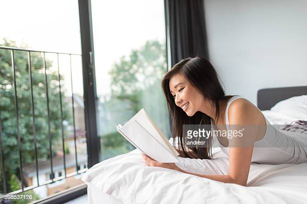 Asian woman reading in bed