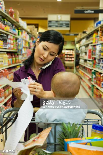 asian woman reading list in grocery store - coupon stock photos and pictures
