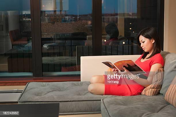 Asian Woman Reading Magazine on Sofa, Inside Apartment at Night