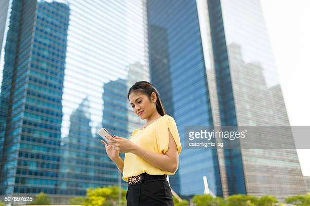 asian woman reading text messages at outdoor - beautiful filipino women stock photos and pictures