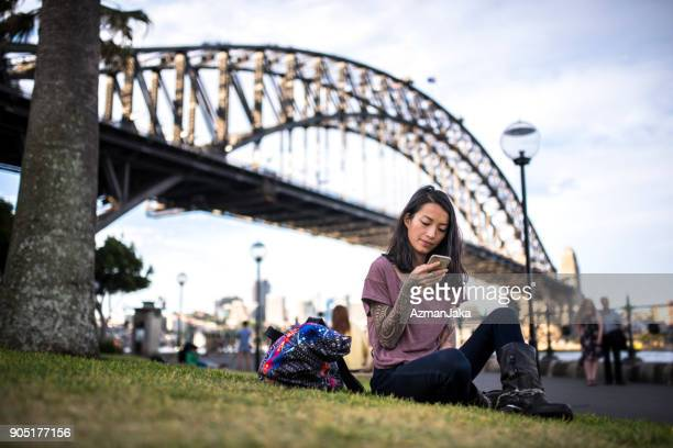 asian woman relaxing and using smart phone in sydney - international landmark stock pictures, royalty-free photos & images