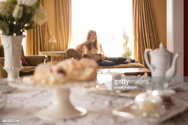 Asian woman relaxing on chaise lounge drinking tea